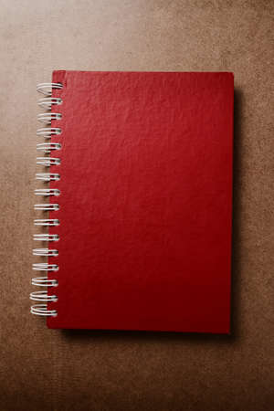 Red notebook on wood texture