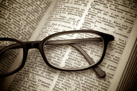 language dictionary: Close-up of old dictionary and black glasses Stock Photo