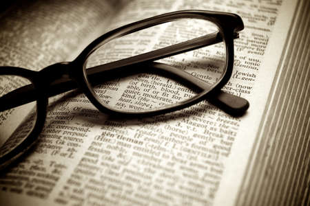 Close-up of old dictionary and black glasses photo