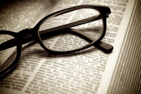definicion: Primer plano de antiguo diccionario y gafas negras