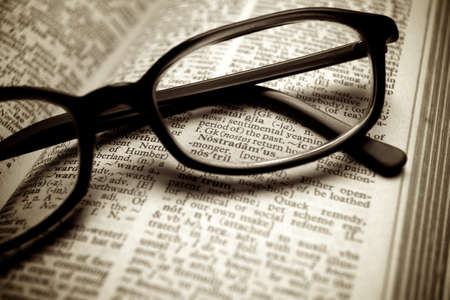 Close-up of old dictionary and black glasses Standard-Bild