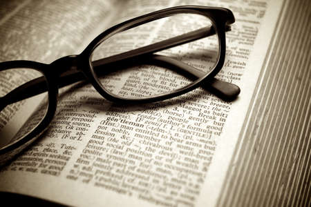 english dictionary: Close-up of old dictionary and black glasses Stock Photo