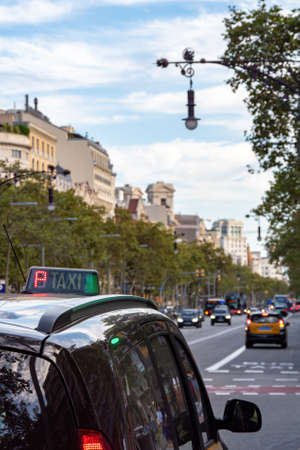 Taxi stands at the traffic light or waits for a passenger on the street of Barcelona