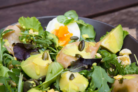 Salad with avocado, dumplings, eggs, pumpkin seeds, arugula and other greens on wooden table in the village. Healthy food concept. Zdjęcie Seryjne
