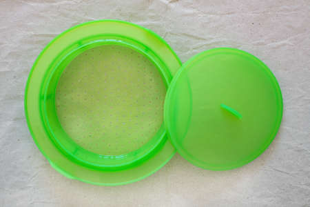 Green silicone insert for healty steam cooking, with cover, on grey paper, top view Zdjęcie Seryjne