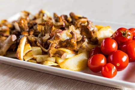 Village breakfast - fried potatoes and mushrooms (chanterelles) with tomatoes on white plate