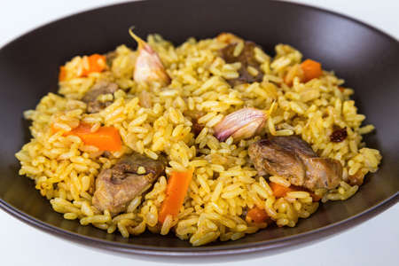 Pilaf with lamb, carrots, onions, garlic, pepper and barberry. A traditional dish of Asian cuisine. Selective focus, isolated on brown plate.