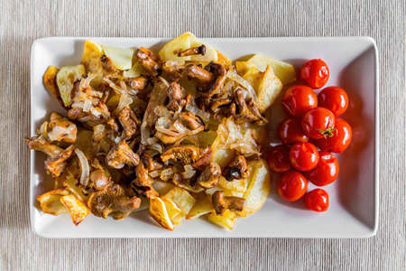 Village breakfast - fried potatoes and mushrooms (chanterelles) with tomatoes on white plate. Top view. Zdjęcie Seryjne
