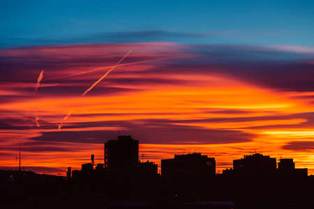 Amazing sunset with orange, pink and red stratus clouds over the city with traces from the planes in the sky. Background for forecast and meteorology concept. Barcelona, Spain.