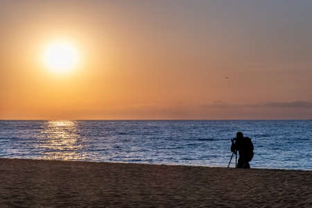 Silhouette of photographer on the beach during sunset Фото со стока