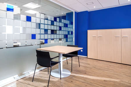 Empty conversation room with table and chairs in modern office interior. Glass wall separates rooms in office.