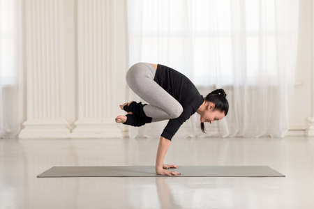 Beautiful young asian woman working out indoors, doing yoga exercise on gray mat, handstand asana, exercise for arms and wrists strength, Crane Crow Pose, Bakasana Banco de Imagens