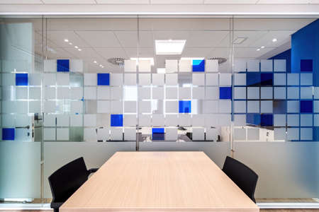 Empty conversation room with table and chairs in modern office interior.