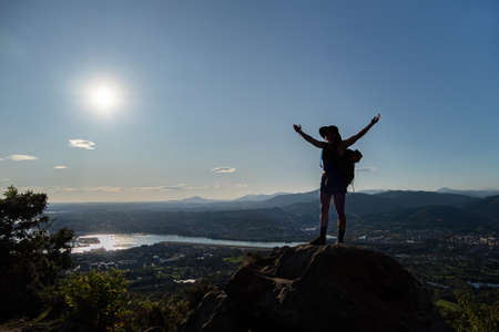 Silhouette of girl in hat, stains on a rock and spreads her hands to the sides. A city, mountains, sea at the background 写真素材