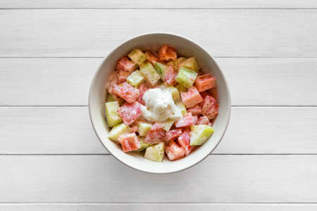 Fresh salad with tomato and cucumber, seasoned with sour cream. Copy space.