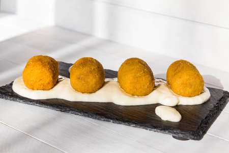 Fried vegetable croquettes with white sauce on black stone plate on wooden background. Unhealthy food. Side view