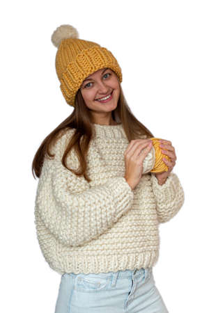 Beautiful happy girl holding in her hands two yarn balls and wearing a sweater and cap, knitted thick thread. Handmade winter clothes. Isolated. Фото со стока