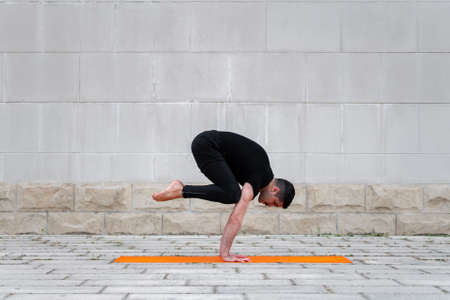 Latin man practicing yoga outdoor in a city, standing in crane pose on orange mat, with gray wall at the background.