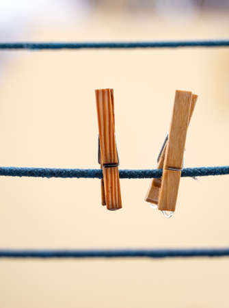 Two wooden clothespins on a blue rope with hanging waterdrops after the rain on blurred background.