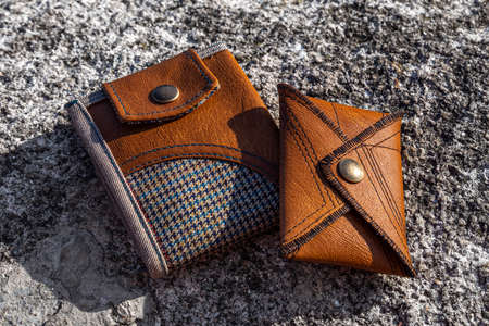 Brown leather wallets, handmade clothing accessories on stone background.