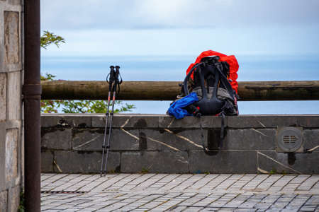 Backpack with red rain cover and walking sticks. Waiting for opening a hostel. Way of St. James, Basque Country, Spain.