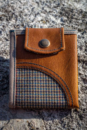 Wallet made of brown leather and checkered fabric on stone background. Handmade mens accessory. Stock Photo