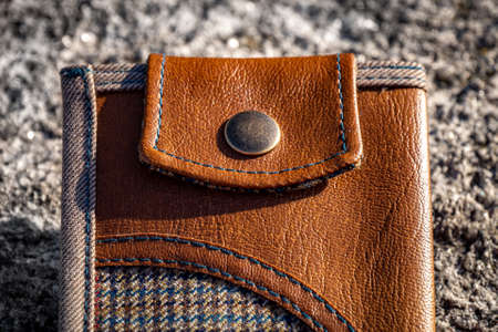 Detail of handmade wallet for money and cards as men's accessory made from brown leather and checkered textile. Men's accessory.