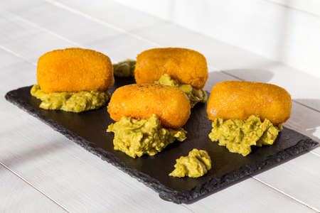 Croquettes fried in oil, with guacamole sauce on black stone plate at sunny kitchen. Side view on white wooden background. Traditional spanish snack.