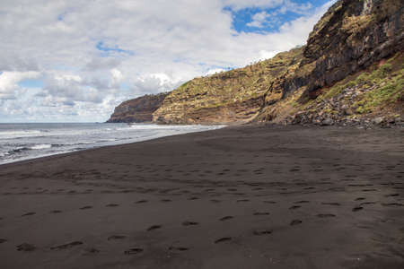 Empty wild beach with foot steps on black sand. Rocks and ocean on Tenerife, Spain