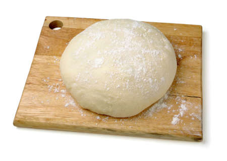 Raw wheat dough on cutting board on a white background