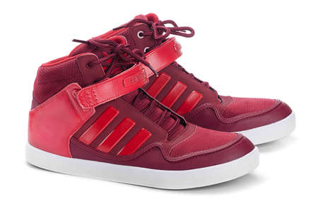 illustrative editorial: SAMARA, RUSSIA - August 17, 2015: Adidas sneakers for running, football, training, in red, showing the Adidas logo and famous three stripes, illustrative editorial Editorial