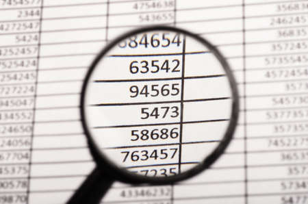Top view of magnifying glass looking at financial report