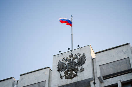 National emblem Russian Federation and flag of the Russian Federation on roof of building