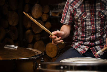 Hands of drummer with sticks and drums close-up