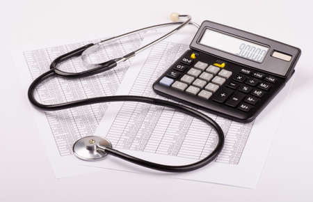 financial statement: Calculator and stethoscope on financial statement