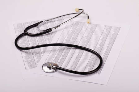 financial statement: Stethoscope on financial statement on a white background