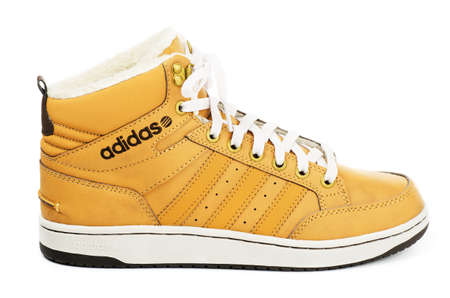 adidas: SAMARA, RUSSIA - January 4, 2016: Adidas Neo sneaker for the winter, in yellow, showing the Adidas logo and famous three stripes, illustrative editorial