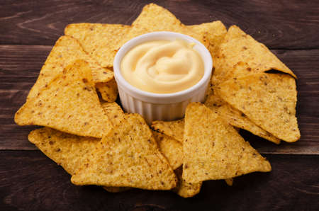 nachos: Nachos and cheese dip on table Stock Photo