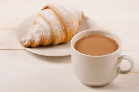 Delicious cup of coffee and croissant on a white background Stock Photo