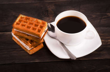 viennese: Coffe, spoon and viennese waffles on a wooden table