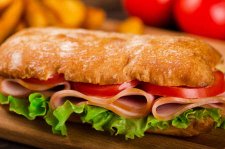 sandwiche: Long sandwiche with lettuce, slices of fresh tomatoes, ham