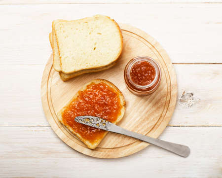 Jar of peach jam with bread on white wooden table background from top view