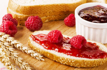 anointed: Raspberry jam with fresh raspberry, bread and wheat on a wooden table