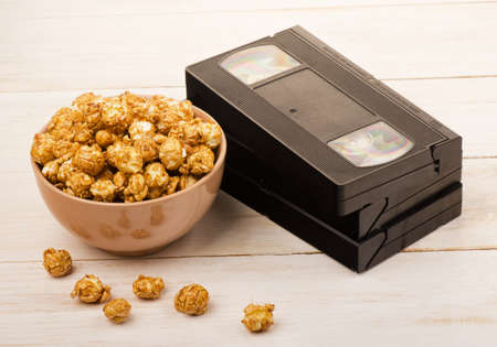 Caramel popcorn near a videotape on wooden background