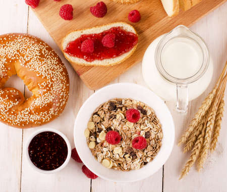 Healthy dietary breakfast with muesli, milk, fresh raspberries, jam and bun on a wooden table, view from above