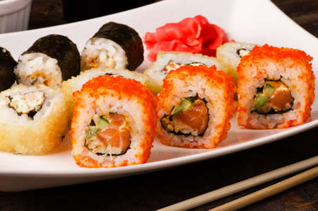 Different sushi roll set california, with salmon and shrimp tempura on a plate