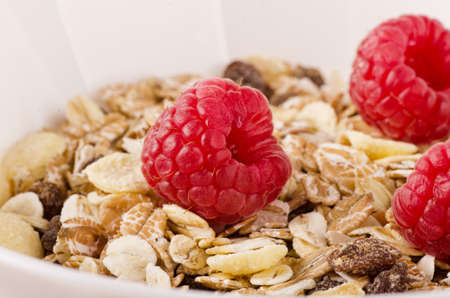 Healthy breakfast. Cereal breakfast with muesli, nuts, and fresh raspberries in a white bowl, close-up Stock Photo