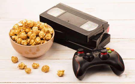 Caramel popcorn near a videotape and gamepad on wooden background Stock Photo
