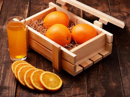Orange lemonade soda juice and oranges in wooden box