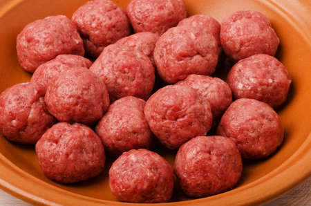 Raw meatballs in plate close-up on a white wooden table background  Stock Photo